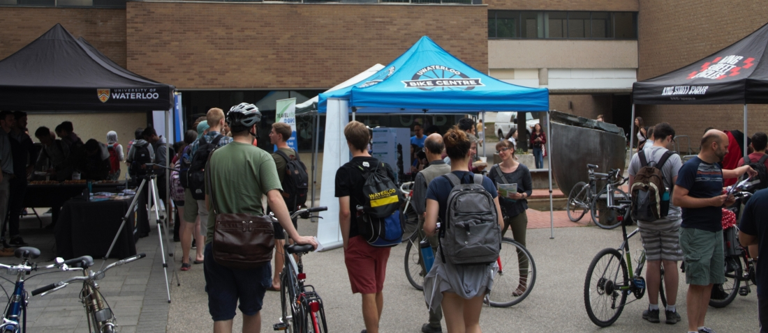 Faculty, staff, and students lining up for free bike tuneups at the Bike Month celebration in June, 2018.